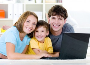 Счастливая молодая семья с  ноутбуком